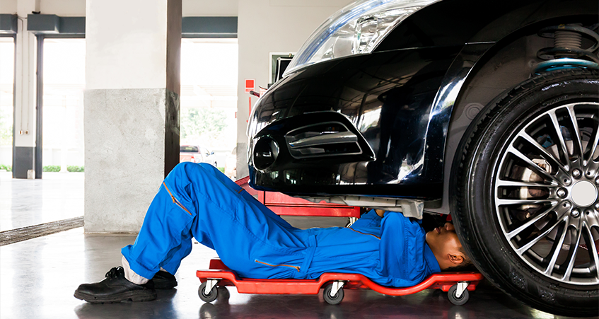 Mechanic under a car in garage - Car Repairs North London
